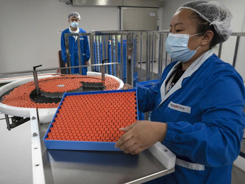 A worker feeds vials for production of a vaccine for COVID-19 at the SinoVac vaccine factory in Beijing. China said on Friday that it is joining the COVID-19 vaccine alliance known as COVAX.