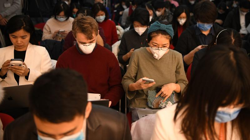 Journalists wearing face masks — in an effort to protect against the coronavirus — gather for a news conference earlier this year in Beijing. Early Wednesday, China said it was planning to pull the press credentials of certain journalists employed by