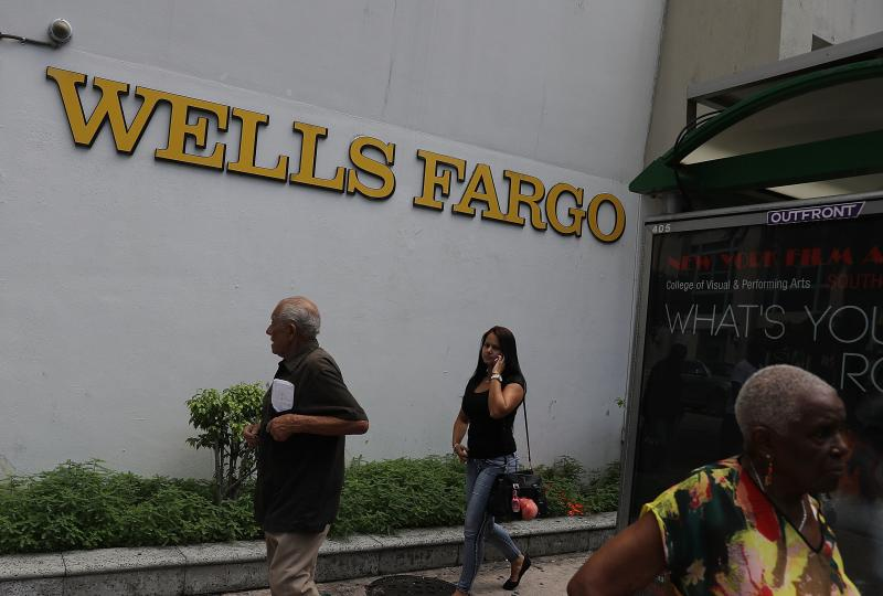 People walk in front of a Wells Fargo branch on Sept. 9, 2016 in Miami, Fla. On Monday, the U.S. Supreme Court ruled that the city of Miami can sue Wells Fargo and Bank of America under the Fair Housing Act for damages caused by allegedly predatory and di