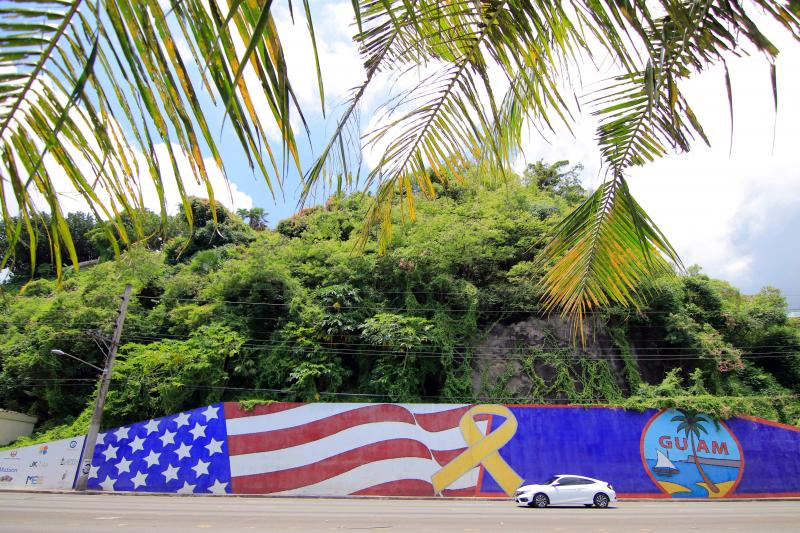 Afternoon traffic passes in front of a mural depicting the U.S. and Guam flags in the Tumon district on the island of Guam.
