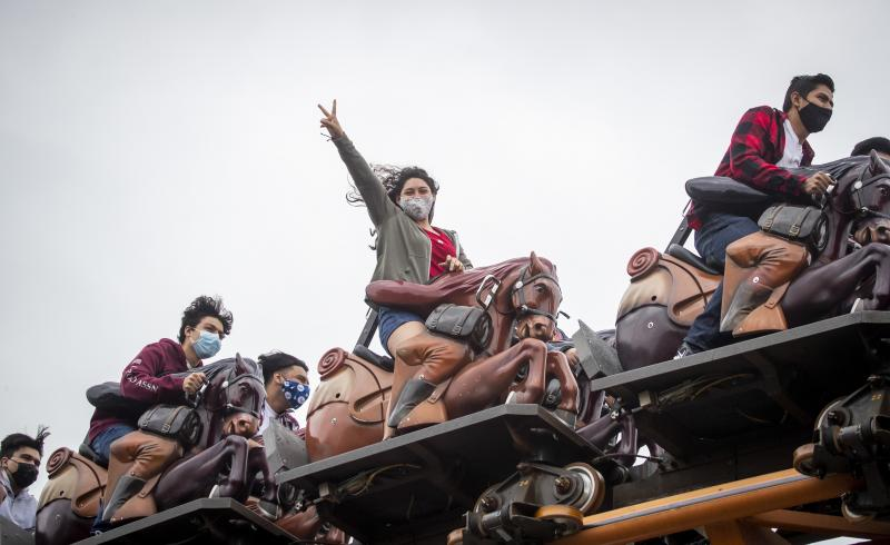 To mask or not to mask: That is the question for vaccinated people as the delta variant surges. The answer may depend on the situation, experts say. Here, these roller-coaster riders mask up at Knott's Berry Farm in Buena Park, Calif.