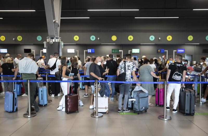 Passengers queue up at Greece's Thessaloniki Makedonia Airport on Sept. 2. Recommendations about physical distancing prove hard to follow at airports — and in the jetway leading to the plane.