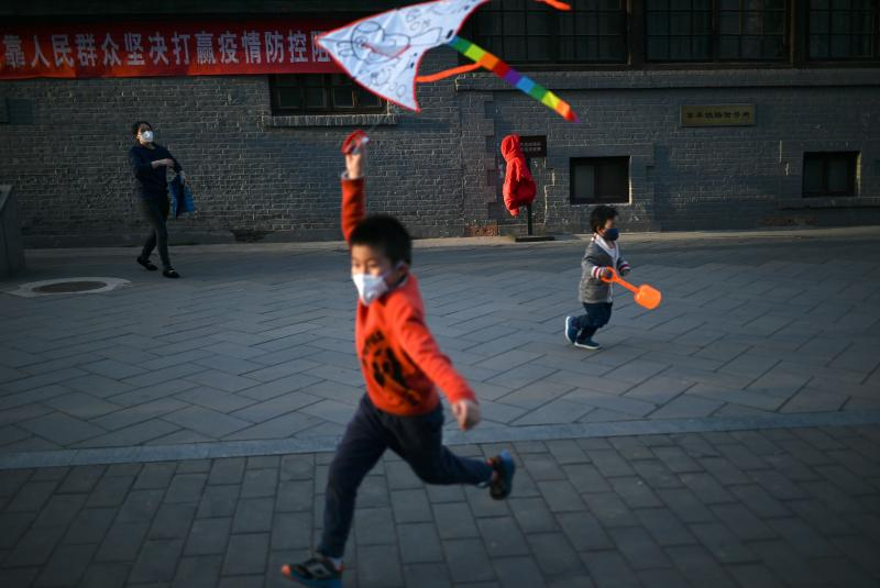 A boy wearing a face mask flies a kite at a park in Beijing. Researchers are studying the response of children to COVID-19.