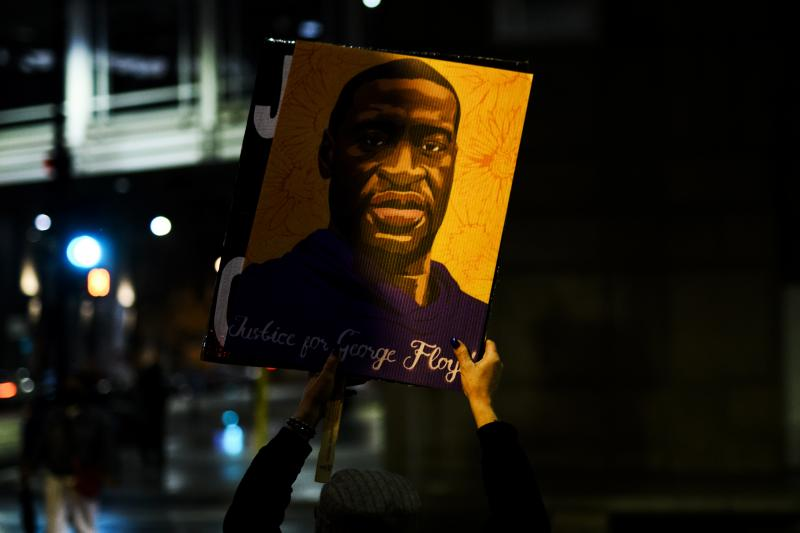 A person holds up a portrait of George Floyd as people gather outside the Hennepin County Government Center on April 9 in Minneapolis