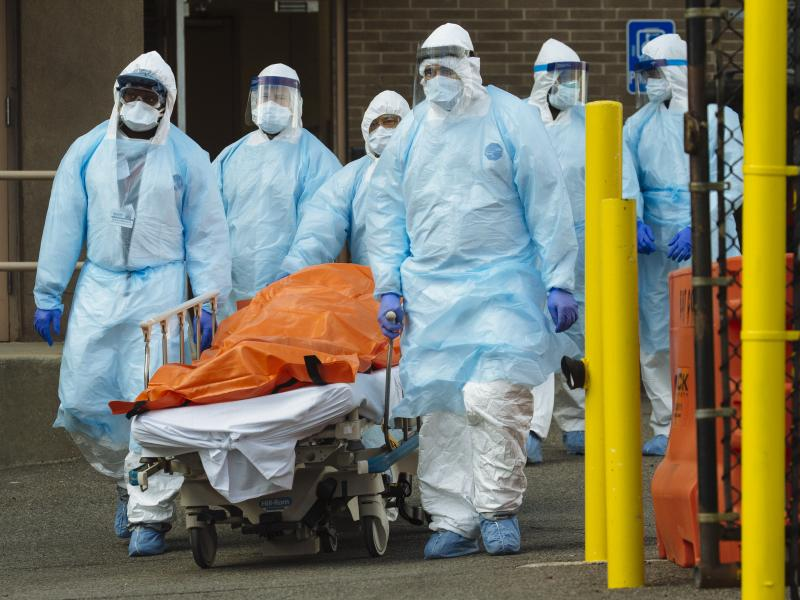 Medical workers in protective clothing move a body to a refrigerated overflow morgue outside the Wyckoff Heights Medical Center in Brooklyn on Thursday.