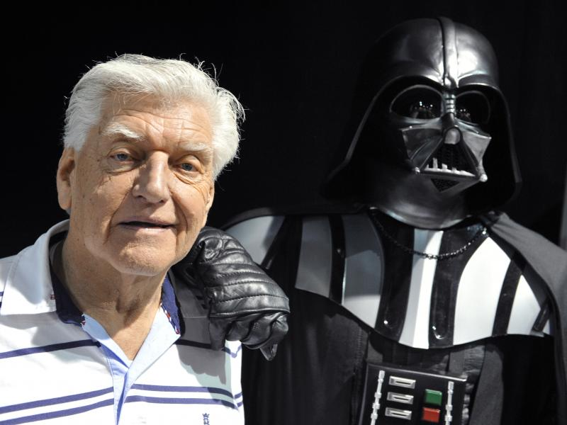 British actor David Prowse, who played Darth Vader in the first Star Wars trilogy, poses with a fan dressed in a Darth Vader costume during a Star Wars convention on April 27, 2013. On Sunday morning, Prowse's management company shared the news of his dea