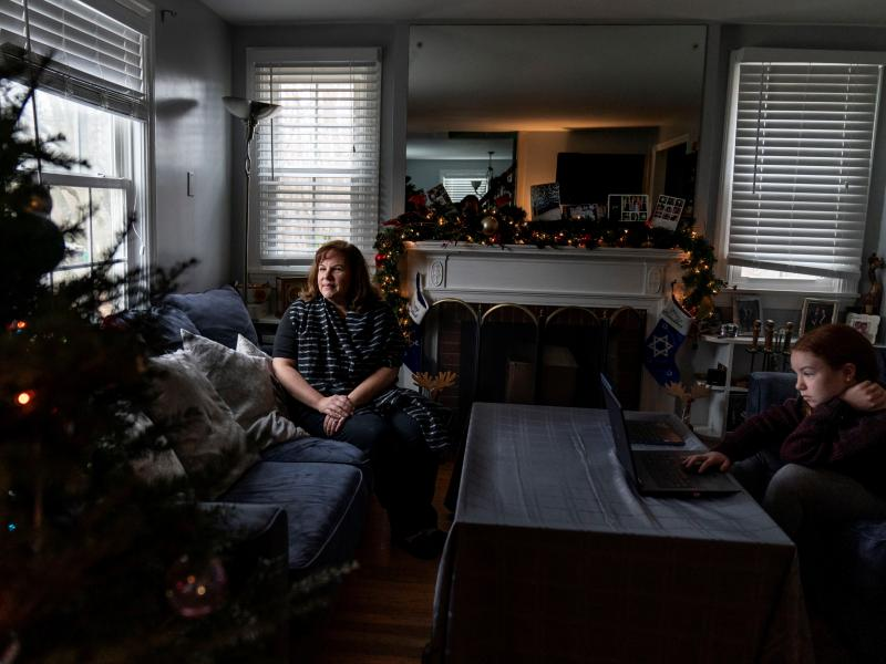 Eileen Carroll, left, sits for a portrait as her daughter, Lily, 11, attends school remotely from their home in Warwick, R.I. on Dec. 16. When Carroll's other daughter tested positive for the coronavirus, state health officials told her to notify anyone h