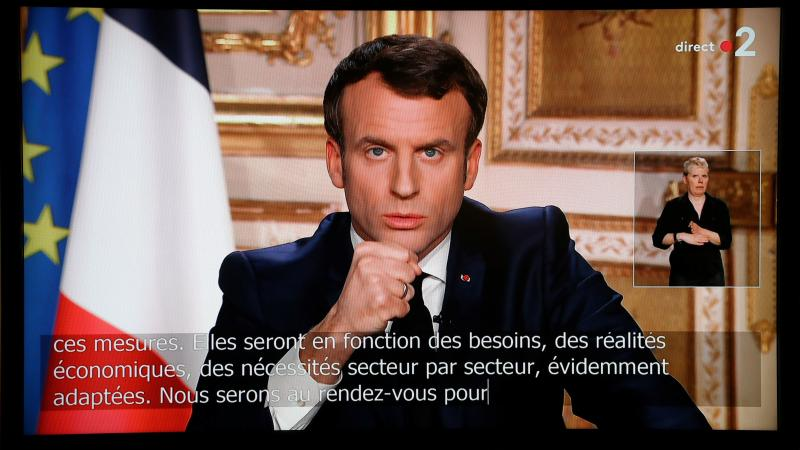 French President Emmanuel Macron is seen on a television screen as he speaks during an address to the nation on the outbreak of COVID-19, caused by the novel coronavirus, on Monday.
