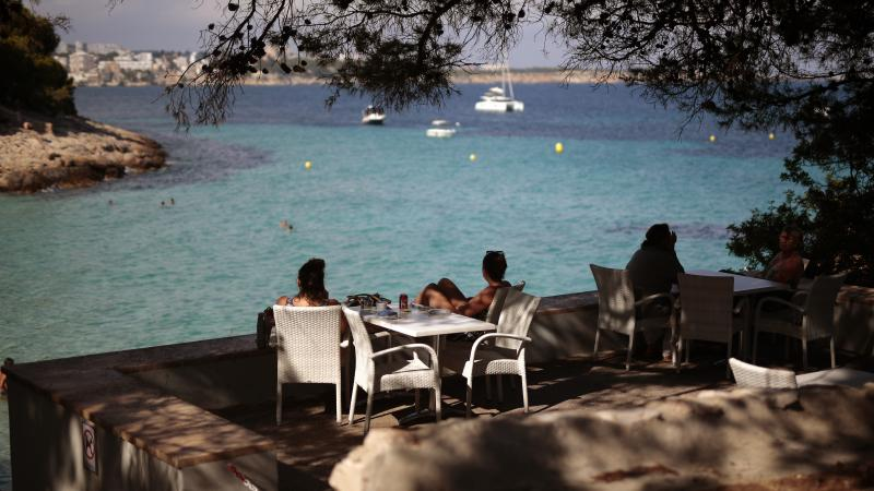 People sit in a terrace bar at the beach in Spain earlier this month, when many internal travel restrictions were lifted. The EU has decided on its first list of approved travel partners, as part of its reopening of external borders.