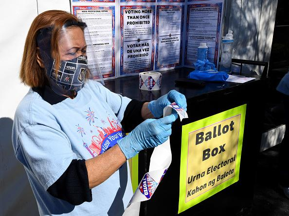 """Volunteer Esmeralda Raymond gets a roll of """"I Voted"""" stickers ready at a polling site in Las Vegas on the first day of in-person early voting on Oct. 17."""