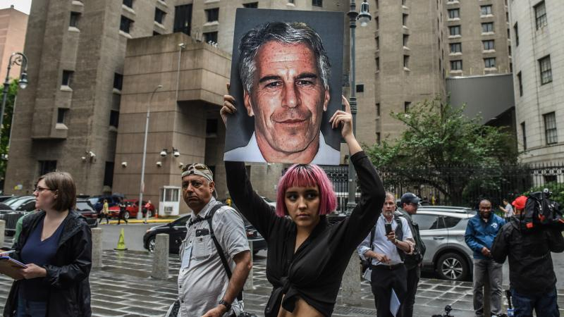 A member of the protest group Hot Mess holds up a sign of Jeffrey Epstein in front of the Metropolitan Correctional Center in New York City in July 2019. Epstein died by asphyxiation in his cell a month later.