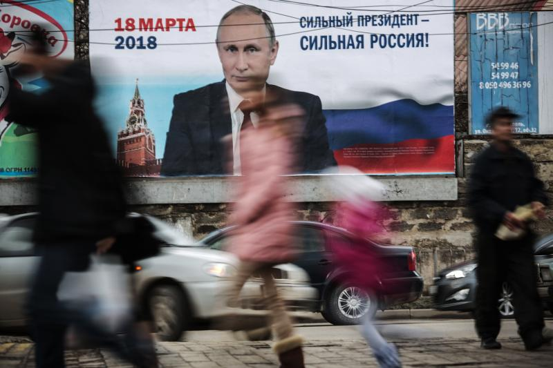 """Pedestrians pass by a billboard with an image of Russia's President Vladimir Putin and lettering """"Strong president - Strong Russia!"""" in Simferopol, Crimea in January."""