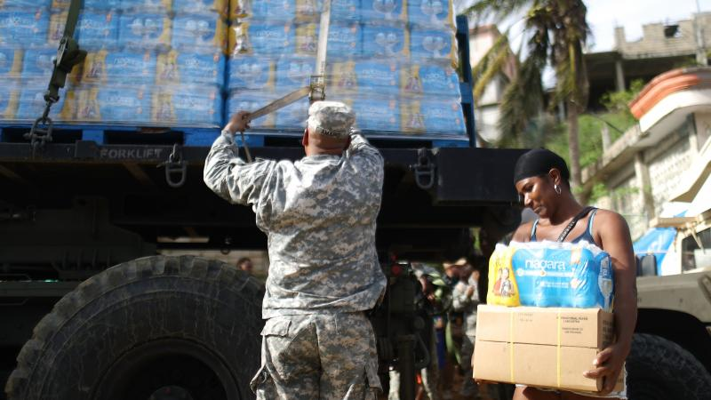 A U.S. Army soldier unloads a shipment of water provided by FEMA as a resident walks past in San Isidro, Puerto Rico.