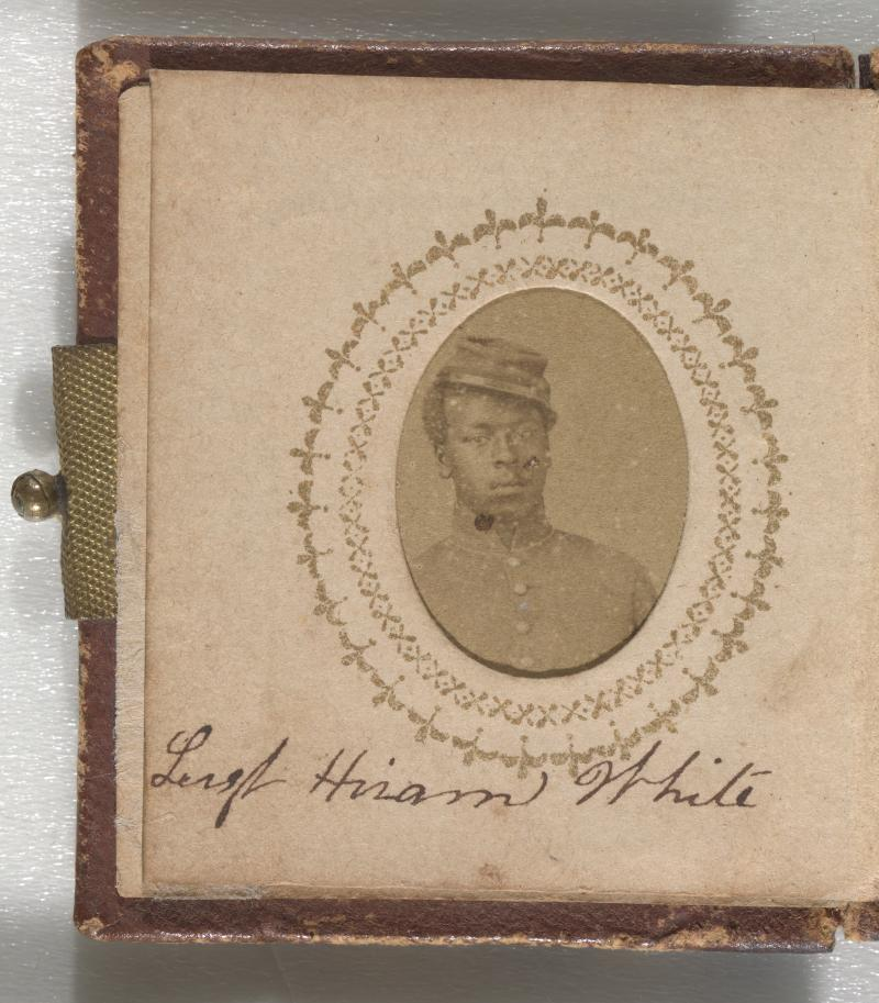 A yellowish brown photograph of Sgt. Hiram White. Sgt. White is wearing a buttoned-up jacket and a kepi in the portrait. He is leaning to his right and his kepi is on the left side of his head. His name is inscribed below the photograph on the same page.