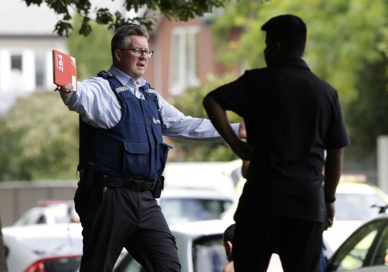 A police officer attempts to move people away from a mosque where shots were fired in Christchurch, New Zealand, on Friday. Police say there are multiple casualties.