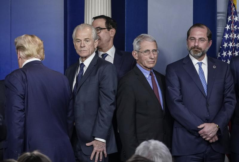 White House economic adviser Peter Navarro (center, left) and Dr. Anthony Fauci, director of the National Institute of Allergy and Infectious Diseases, stand back to back after a White House Coronavirus Task Force briefing on March 9. Navarro wrote an opi