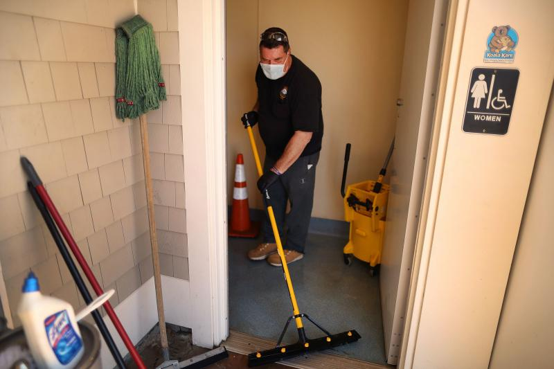 Town worker Steve Crowley washes and disinfects the public restroom at Mayflower Beach, in Dennis, Mass., last week. As stay-at-home restrictions are lifting, many people are concerned about using public restrooms.