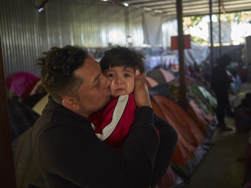 Juan Carlos Perla of El Salvador kisses his 10-month-old son, Joshua, inside a migrant shelter in Tijuana, Mexico, where they await their asylum hearing in San Diego.