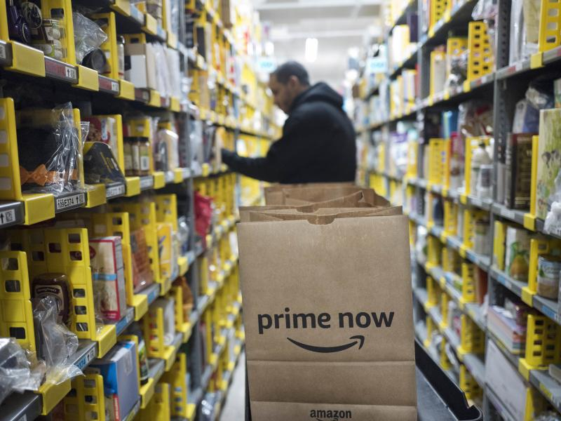 "A clerk pick an item for a customer order at the Amazon Prime warehouse in New York. Amazon Empire director James Jacoby describes the pace of work within the company's warehouses as ""incredibly grueling."""