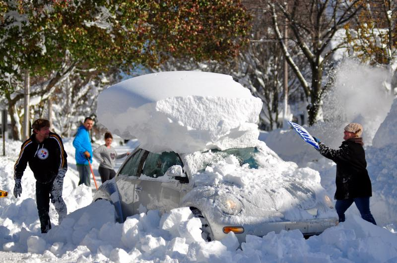 Michael Palmer and Carin Schultz work to clear her car of snow and remove it from Union street on Thursday in the Buffalo suburb of Hamburg.