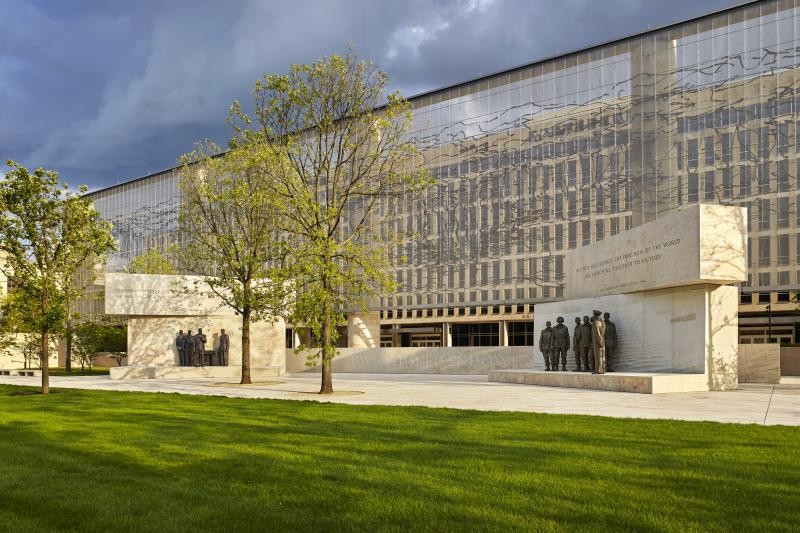 "The Dwight D. Eisenhower Memorial in Washington, D.C., will be dedicated on Thursday. A stainless steel, woven ""tapestry"" made by artist Tomas Osinski stands behind the statues and depicts the cliffs at Normandy."