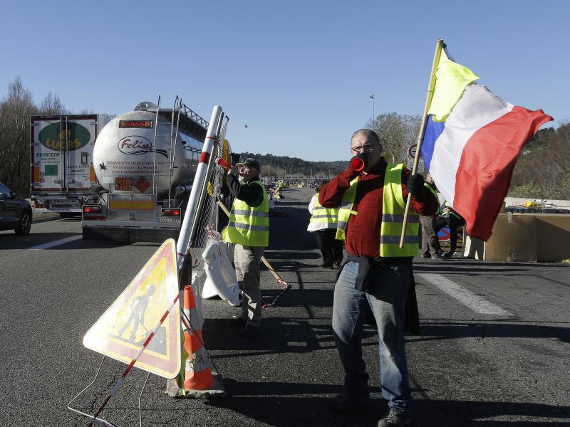"""The French government is suspending a planned fuel tax hike, after """"yellow vest"""" demonstrators took to the streets for months of protests. On a motorway near Aix-en-Provence, France, on Tuesday, demonstrators set up a barrier."""