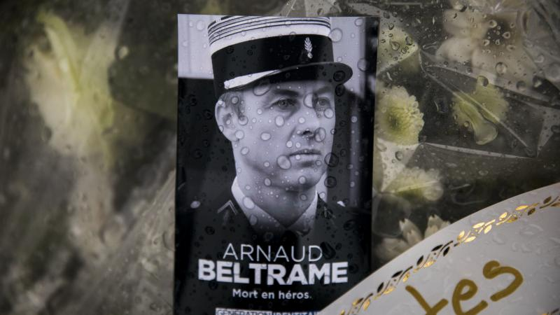 A photo of Lt. Col. Arnaud Beltrame rests on a bunch of flowers at the main gate of the police headquarters in Carcassonne, France. On Sunday, a man was arrested on charges of apologizing for terrorism after seemingly praising Beltrame's death on social m
