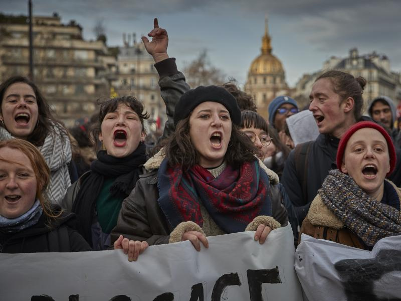 Protestors chant and sing against President Emmanuel Macron during a rally in Paris as thousands take to the streets to protest against pension reform on Tuesday.