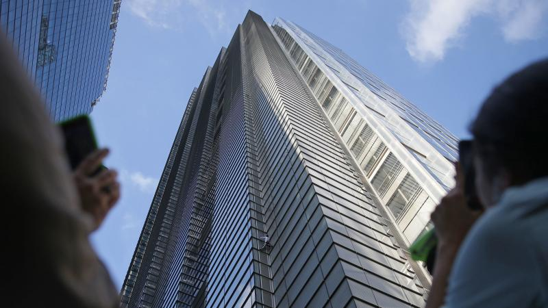 People watch as French urban climber Alain Robert ascends the 46-story Heron Tower in central London on Thursday.