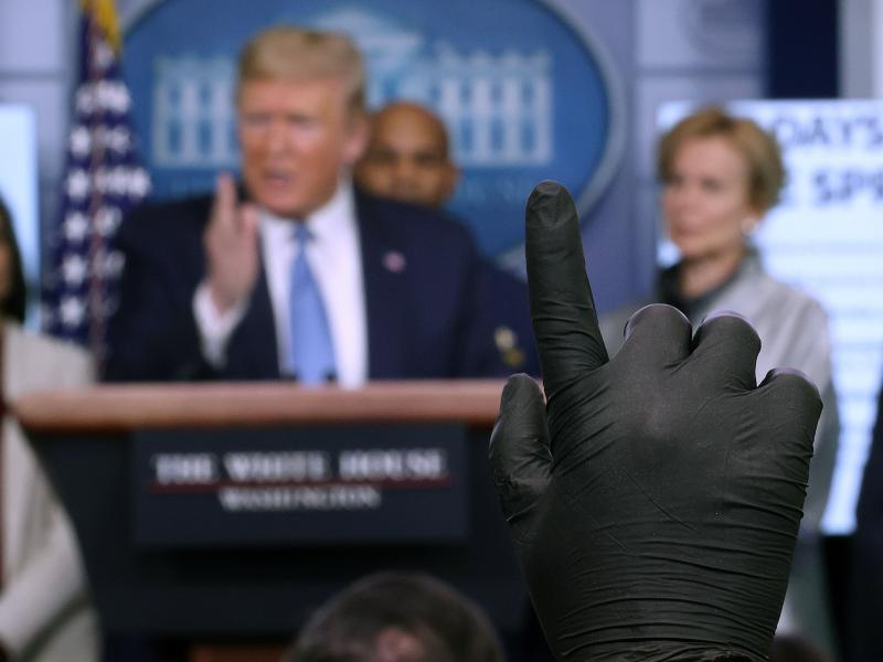 A reporter wearing a latex glove raises his hand to ask President Trump a question during a coronavirus briefing at the White House on March 16.