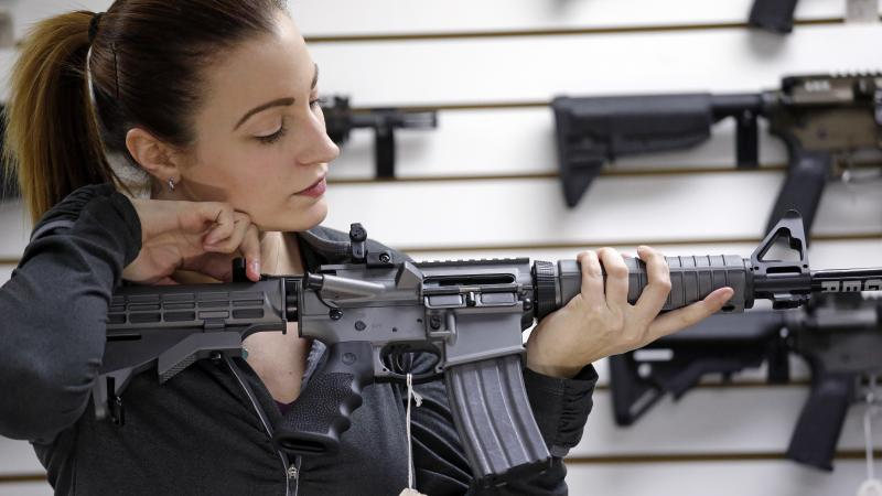Gun shop owner Tiffany Teasdale-Causer demonstrates a Ruger AR-15 semi-automatic rifle. The Supreme Court hasn't ruled on whether assault-style weapons can be banned.