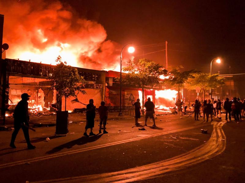Flames rise from a liquor store and shops near the 3rd Police Precinct in Minneapolis on Thursday , during a protest over the death of George Floyd.