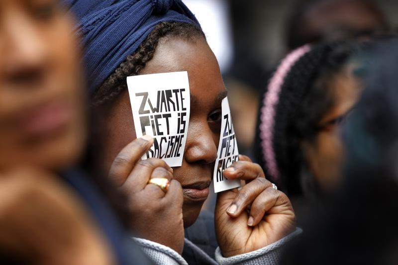 """A demonstrator holds a sign reading """"Black Pete Is Racism"""" during a 2013 demonstration in Amsterdam. Zwarte Piet or Black Pete is traditionally depicted by white people wearing blackface, Afro wigs and red lipstick."""