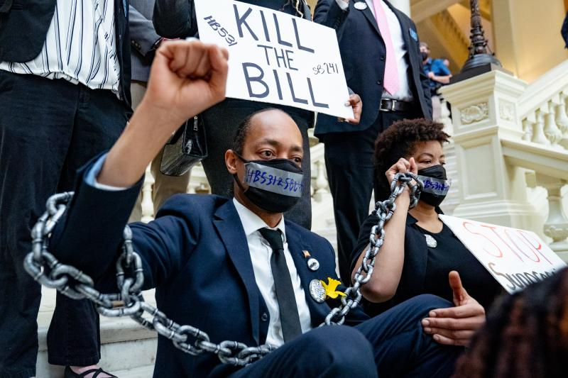 Demonstrators who oppose voting bills that, among other things, would end no-excuse absentee voting, wear chains while holding a sit-in inside the Georgia Capitol in Atlanta on Monday.