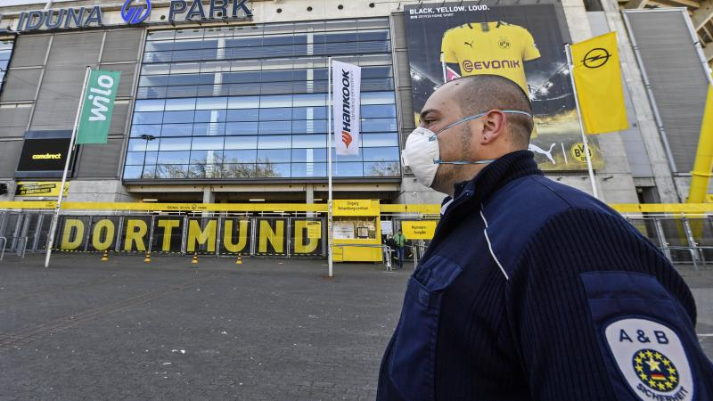 Security with face masks stand in front of the Signal Iduna Park, where a temporary coronavirus treatment center opened in Dortmund, Germany, Saturday. Germany has the fourth-most COVID-19 cases in the world and demand for medical supplies has skyrocketed