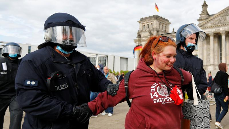 German police detain a demonstrator during a protest against the government's restrictions to prevent the spread of the coronavirus in front of the Reichstag in Berlin on Saturday.