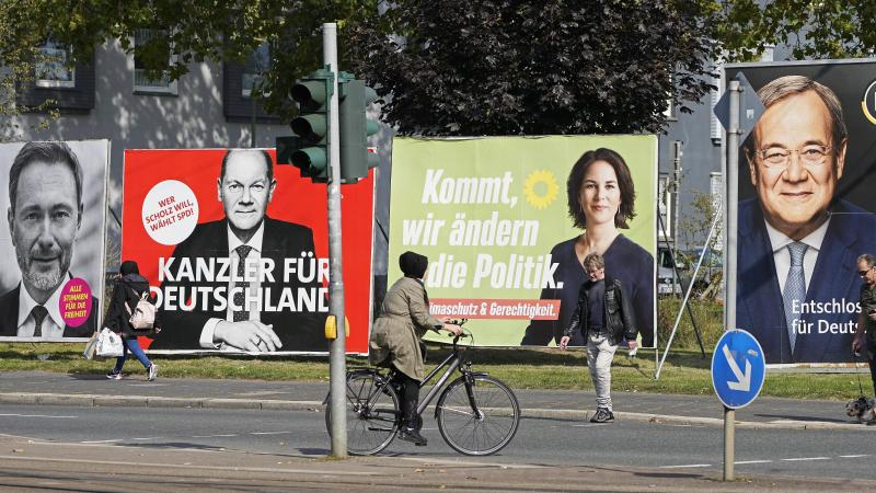 On Thursday, people in Gelsenkirchen, Germany, pass election posters of chancellor candidates Armin Laschet (from right) of the Christian Democratic Union, Annalena Baerbock of the Greens, Olaf Scholz of the Social Democratic Party and Christian Lindner o