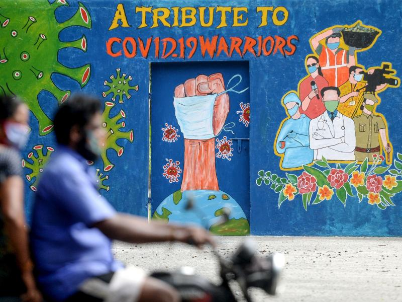 A mural in Chennai, India, celebrates workers on the front lines against the coronavirus pandemic. The global case count crossed the 20 million threshold on Monday, with the U.S., Brazil and India in the lead.