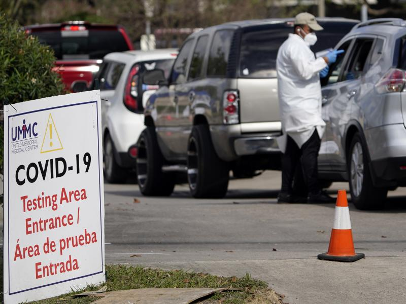 A healthcare worker processes people in line at a United Memorial Medical Center COVID-19 testing site on Nov. 19, in Houston. Texas is rushing thousands of additional medical staff to overworked hospitals as the number of hospitalized COVID-19 patients i