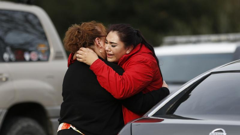 Vanessa Flores (right) embraces another woman Friday after she leaves the locked-down Veterans Home of California in Yountville, Calif., during a hostage situation. Law enforcement officers found a gunman and three hostages dead after a lengthy standoff.