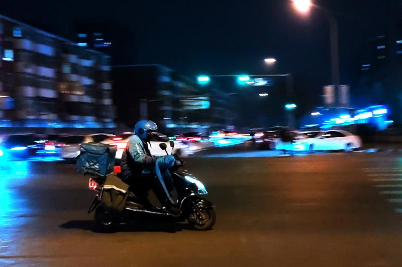 A courier delivers goods at night on a street in Beijing in February.