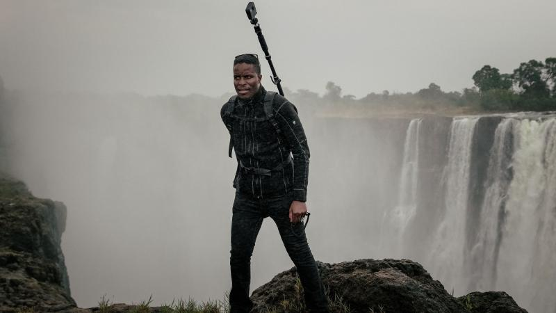 Tawanda Kanhema in 2018 wearing Google Street View camera gear at Victoria Falls in Zimbabwe.