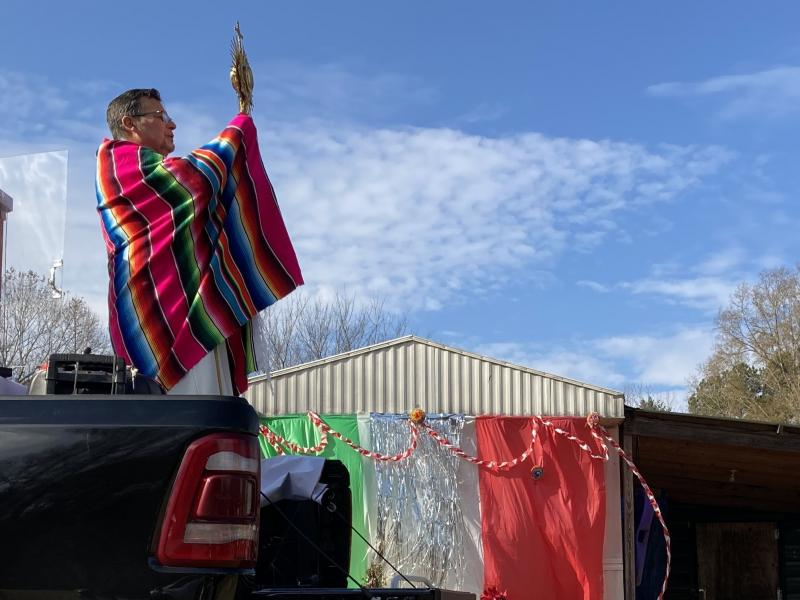 Father Julio Martinez raises the Blessed Sacrament from the back of a pickup truck in Ramseur, N.C.