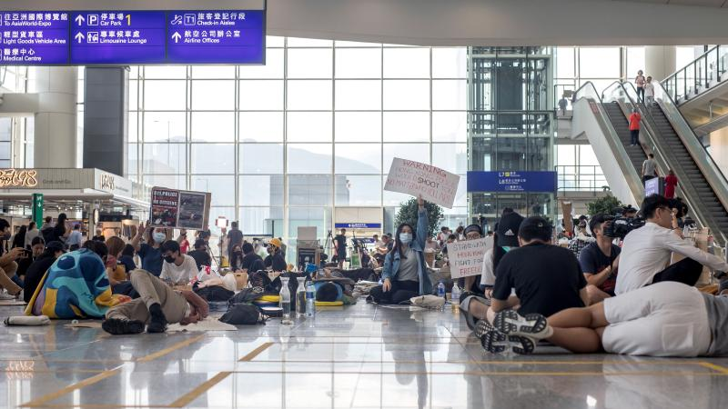 Demonstrators sit and lie on the arrival hall floor at Hong Kong International Airport on Wednesday.