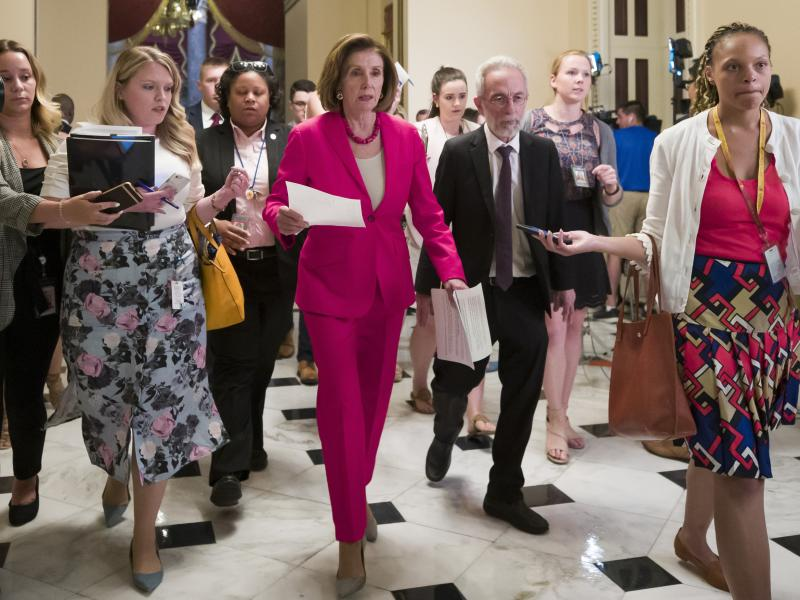 """Speaker Nancy Pelosi of California walks to the House floor Thursday. In a letter to Democratic lawmakers she announced the House would """"reluctantly"""" pass a Senate version of an emergency immigration aid package."""