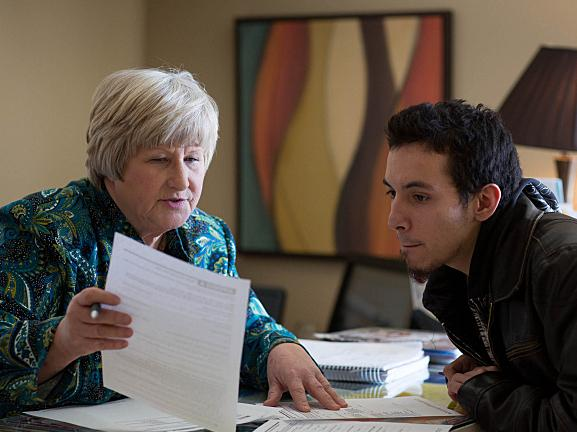 Becky Fink, a MNsure navigator, helps Mic-Ryan Freeman, 22, fill out a paper application for health insurance in February at Nucleus Clinic in Coon Rapids, Minn.