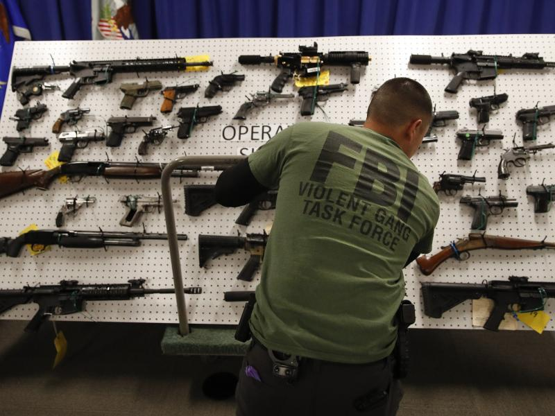 An FBI agent displays seized firearms from a gang investigation. Digital facial recognition helped the bureau track down an MS-13 member wanted in connection with murder.