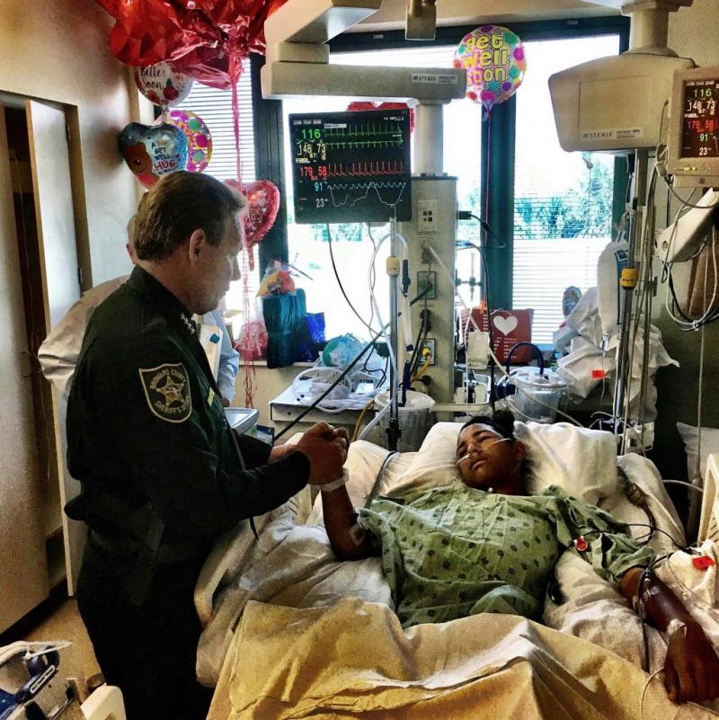 Sheriff Scott Israel, holds the hand of Anthony Borges, 15, a student at Marjory Stoneman Douglas High School in a photo released Feb. 18. Anthony was the last Parkland survivor to be released from the hospital and now his lawyer is preparing a lawsuit ag