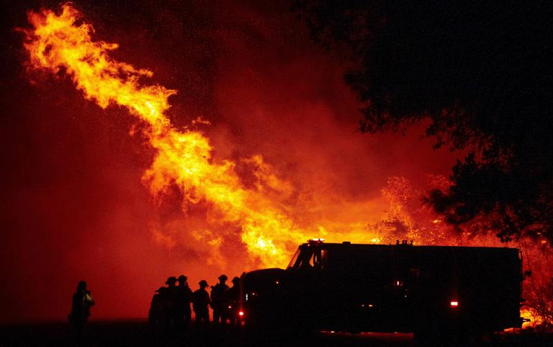 Firefighters watch as flames tower over their truck Wednesday at the Bear Fire in Oroville, Calif. The 2020 fire season is off to a staggering start, far outpacing last year.