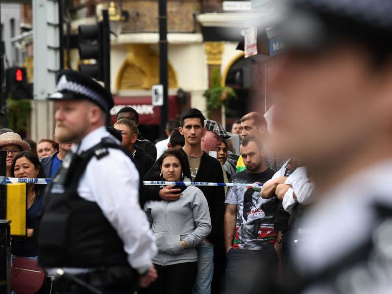 Londoners stand behind a cordon in the East Ham district on Sunday, following a police raid investigating Saturday's terror attacks in Central London.